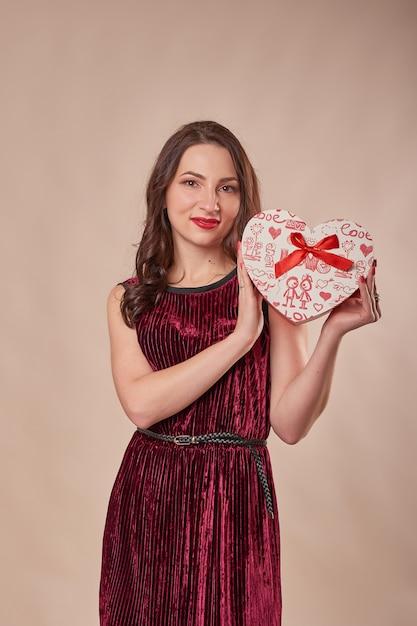 Portret van vrolijke vrouw in rode de giftdoos van de kledingsholding Premium Foto