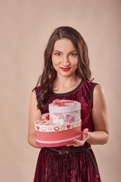 Portret van vrolijke vrouw in rode de giftdozen van de kledingsholding Premium Foto