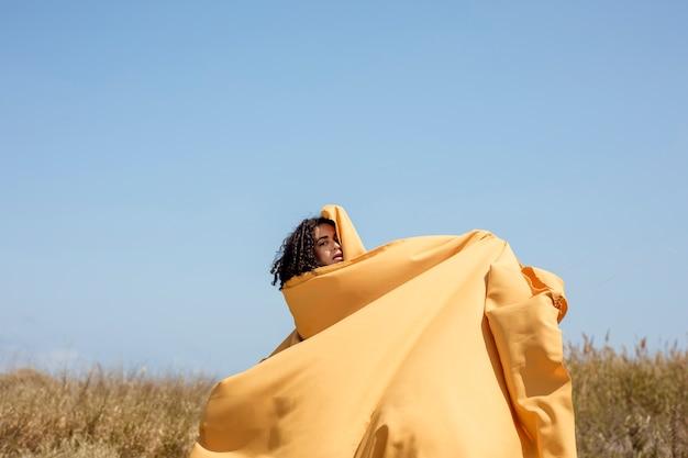 Portret van vrolijke vrouw met gele doek in de natuur Gratis Foto