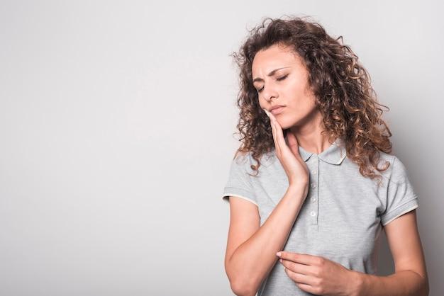 Portret van vrouw die aan tandpijn tegen witte achtergrond lijdt Gratis Foto