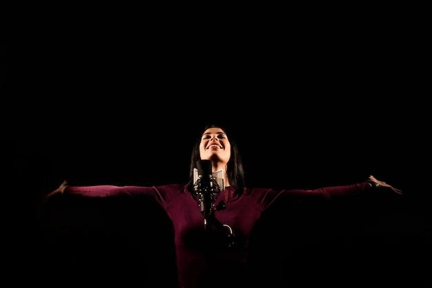Portret van vrouw die een lied in een professionele studio registreert Premium Foto