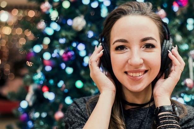 Portret van vrouw die hoofdtelefoons draagt dichtbij kerstmisboom Gratis Foto