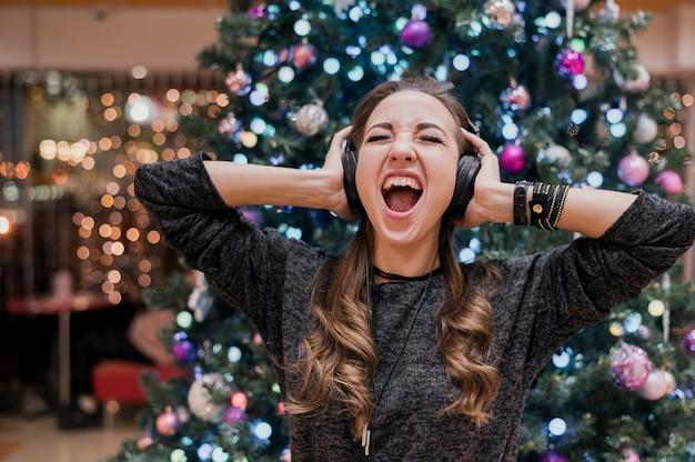Portret van vrouw die hoofdtelefoons draagt en dichtbij kerstmisboom schreeuwt Gratis Foto
