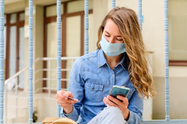 Portret van vrouw die met gezichtsmasker zakken controleert Gratis Foto
