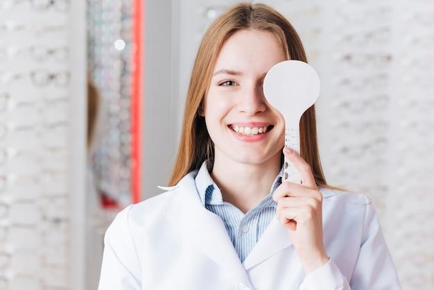 Portret van vrouw die test van oogvisie doet Premium Foto