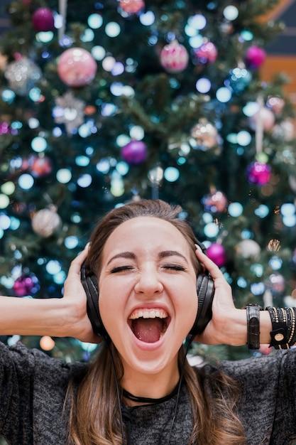 Portret van vrouw met hoofdtelefoons en het schreeuwen dichtbij kerstmisboom Gratis Foto