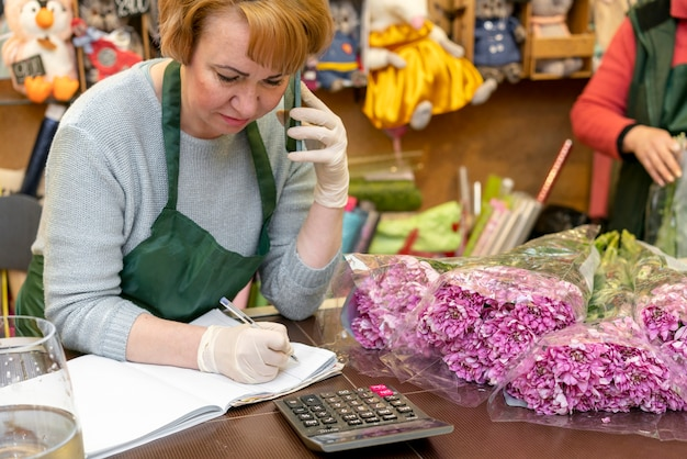 Portret van vrouw verantwoordelijk voor bloemenwinkel Gratis Foto