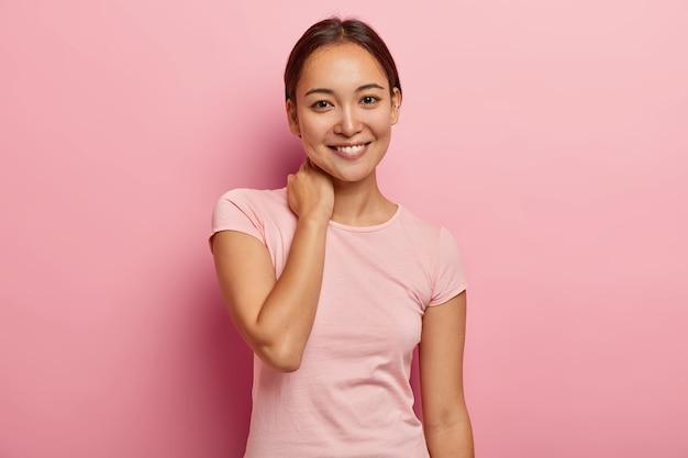 Portret van vrouwelijk meisje met aangename glimlach, zachte blik, nek aanraakt, gezichtsuitdrukking verheugd heeft, aangenaam gesprek heeft met goede vriend, gekleed in casual outfit, geïsoleerd op roze muur Gratis Foto