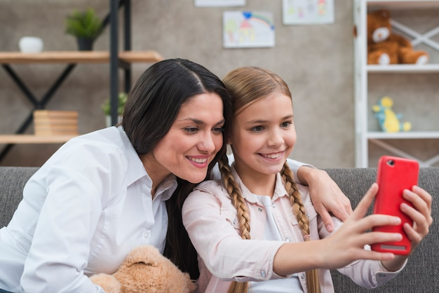 Portret van vrouwelijk psycholoog en meisje die selfie uit mobiele telefoon nemen Gratis Foto