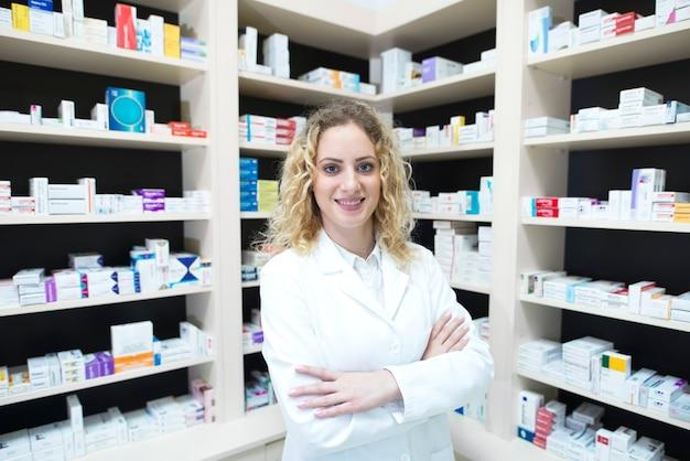 Portret van vrouwelijke apotheker in drogisterij staande voor planken met medicijnen Gratis Foto