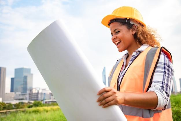 Portret van vrouwelijke architect permanent met bouwtekeningen papierrol in het openbare park. Premium Foto