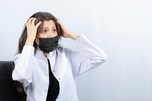 Portret van vrouwelijke arts in medisch masker en witte laag die met iemand ruzie maken. Gratis Foto