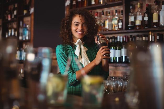 Portret van vrouwelijke barman die een cocktaildrankje in cocktailshaker mengt Premium Foto