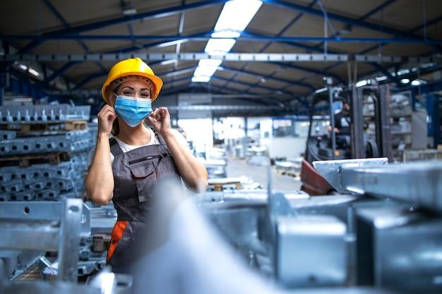 Portret van vrouwelijke fabrieksarbeider in uniform en veiligheidshelm die gezichtsmasker draagt in industriële productie-installatie Gratis Foto