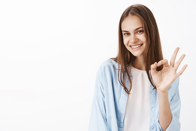 Portret van vrouwelijke gelukkig en zelfverzekerd stijlvolle vrouwelijke brunette in blauwe trendy blouse over wit t-shirt met oke of ok gebaar en lachend met zelfverzekerde blik Gratis Foto