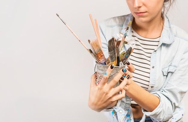 Portret van vrouwelijke kunstenaar met penselen Gratis Foto