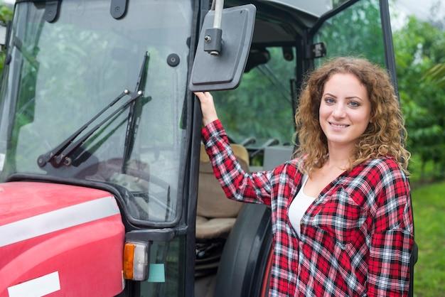 Portret van vrouwelijke landbouwer die zich door de tractormachine in boomgaard bevindt Gratis Foto