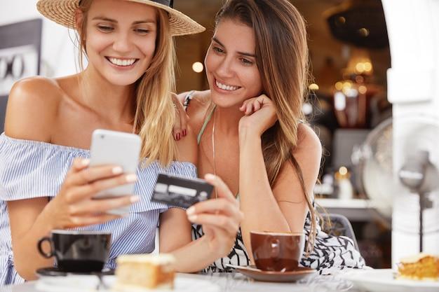 Portret van vrouwelijke modellen maken online winkelen, gebruiken slimme telefoon, creditcard, zitten samen in café-interieur met aromatische koffie, hebben een positieve uitstraling. beste vrienden recreëren samen, gebruiken technologieën Gratis Foto