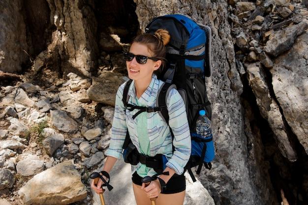 Portret van vrouwelijke wandelaar in zonnebril met rugzak Premium Foto
