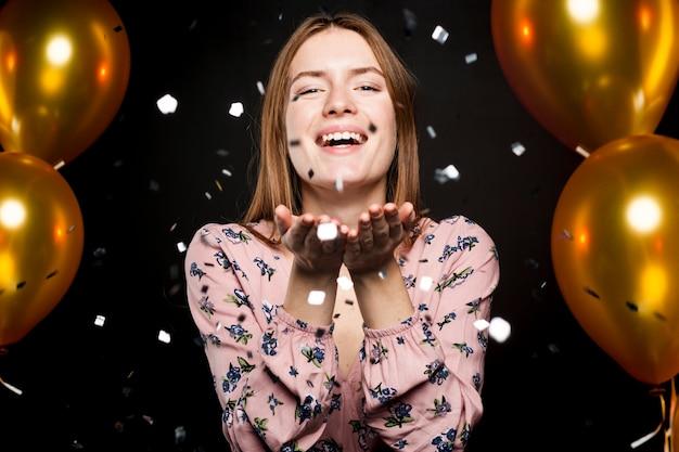 Portret van vrouwen blazende confettien bij partij Gratis Foto