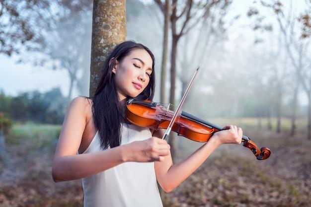 Portret van vrouwenkleding in witte lange kleding die de viool, de zachte nadruk en de uitstekende toon spelen Premium Foto