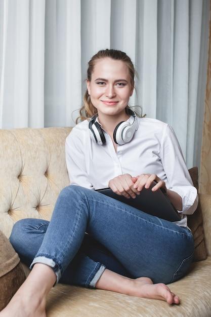 Portret van vrouwenzitting op bank en het luisteren aan muziek Premium Foto