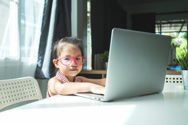 Portret van weinig aziatisch meisje met laptopcomputer voor online toepassing thuis studeren. homeschooling, online leren of onderwijsconcept Premium Foto