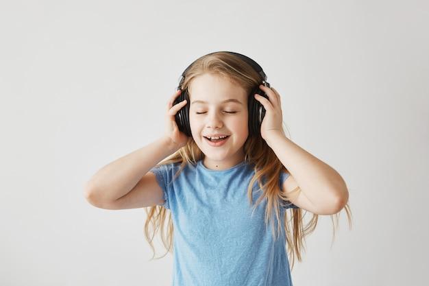 Portret van weinig blondemeisje in blauw overhemd die met grote draadloze hoofdtelefoons spelen, aan muziek luisteren, lied zingen en met gesloten ogen dansen terwijl niemand naar huis gaat. Gratis Foto