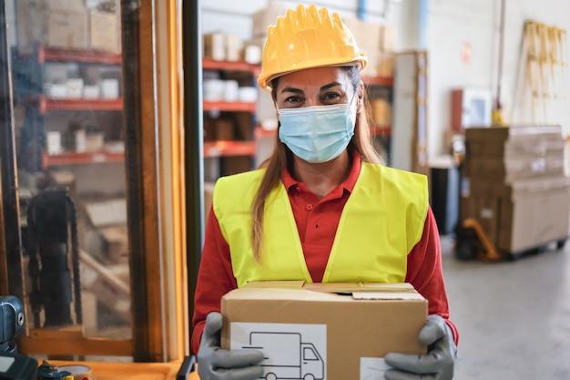 Portret van werknemer vrouw met kartonnen doos in magazijn terwijl het dragen van veiligheidsmasker - focus op gezicht Premium Foto