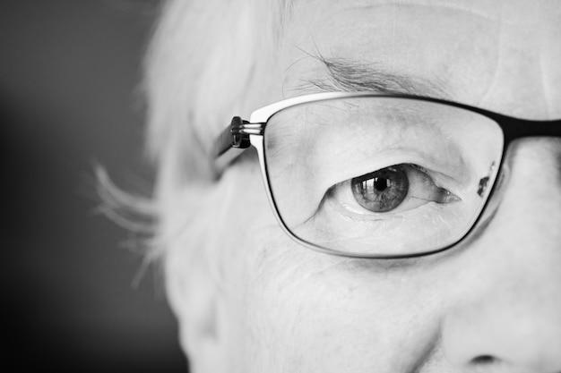 Portret van witte bejaardeclose-up op ogen die specatac dragen Gratis Foto