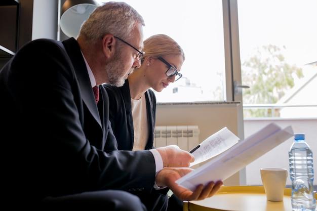 Portret van zakelijke man en vrouw zitten in kantoor contract bespreken Gratis Foto