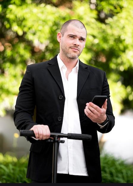 Portret van zakenman het stellen met autoped Gratis Foto