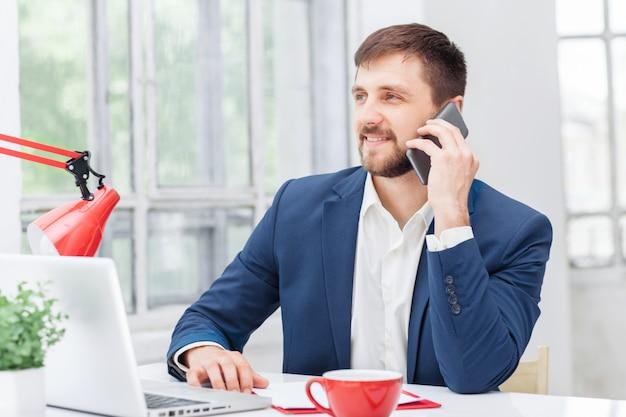 Portret van zakenman praten over telefoon in kantoor Gratis Foto