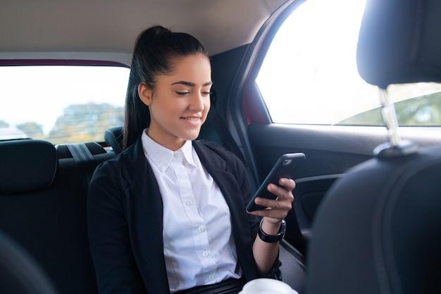 Portret van zakenvrouw met behulp van haar mobiele telefoon op weg naar het werk in een auto. bedrijfsconcept. Gratis Foto