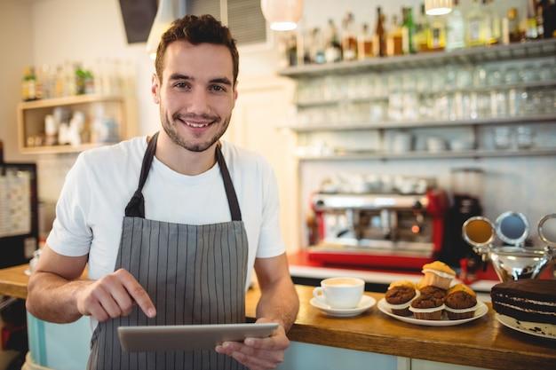 Portret van zekere barista die digitale tablet gebruiken bij koffie Premium Foto