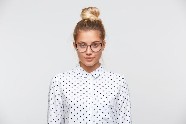 Portret van zelfverzekerde aantrekkelijke jonge vrouw met broodje draagt polka dot shirt en bril Gratis Foto