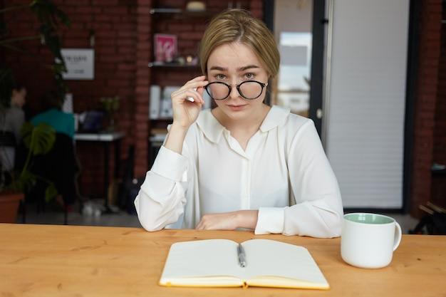 Portret van zelfverzekerde jonge vrouw formele kleding en ronde bril zitten in café met lege beurt en mok op tafel, kijken met onderzoekende nieuwsgierige gezichtsuitdrukking Gratis Foto