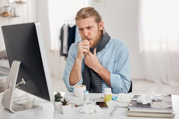 Portret van ziek zieke bebaarde mannelijke manager hoest, heeft verkoudheid en griep. jonge blonde man heeft lopende neus, hoest en ernstige verkoudheid, zit op de werkplek voor computerscherm. ziekte en infectie Gratis Foto