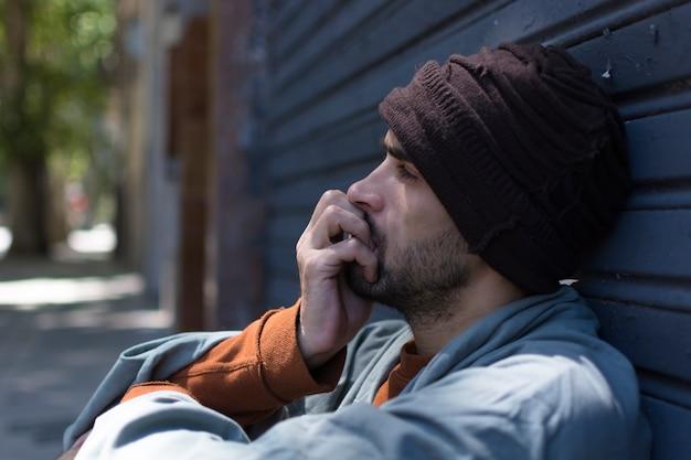 Portret van zijdelings dakloze mens die wordt verstoord Gratis Foto