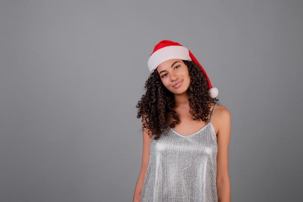 Portret van zwarte die zilveren kleding en kerstmishoed draagt die over grijs wordt geïsoleerd Premium Foto