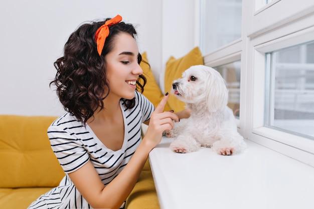 Portret verbazingwekkende vrolijke modieuze jonge vrouw spelen met hondje in modern appartement. plezier hebben met huisdieren, glimlachen, opgewektheid, thuis Gratis Foto