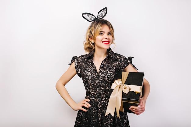 Portret vrolijk meisje met lang donkerbruin krullend haar, luxe zwarte jurk. vieren, verjaardagsfeestje, plezier maken met geschenkdoos. Gratis Foto
