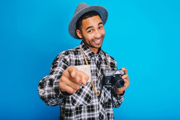 Portret vrolijke stijlvolle man met kaart en camera glimlachen. toerist, plezier hebben, reizen, opgewekte stemming, glimlachen, jorney, vakanties, echte positieve emoties uitdrukken. Gratis Foto