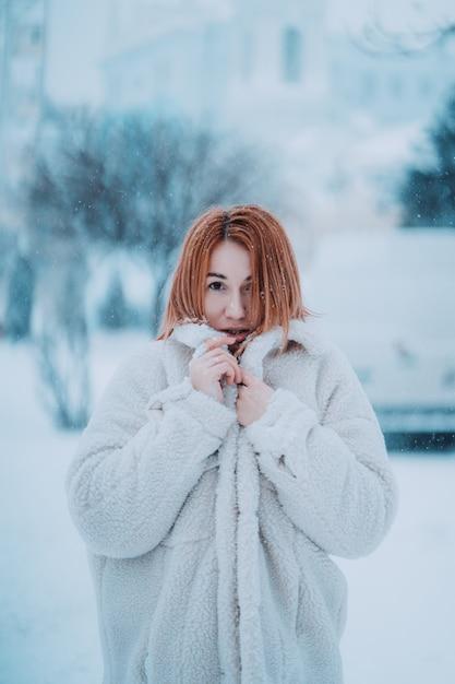 Portret vrouwelijk model buiten in eerste sneeuw Gratis Foto