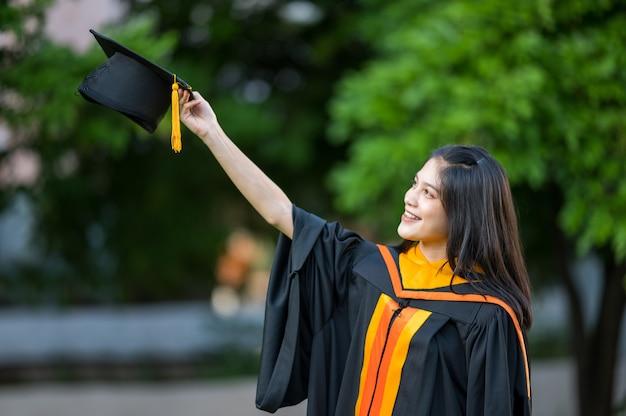 Portret vrouwelijke afgestudeerde academicus met een zwarte hoed Premium Foto