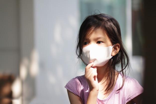 Portretbeeld van aziatisch basisschoolmeisje dat masker draagt voor preventie van coronavirus Premium Foto
