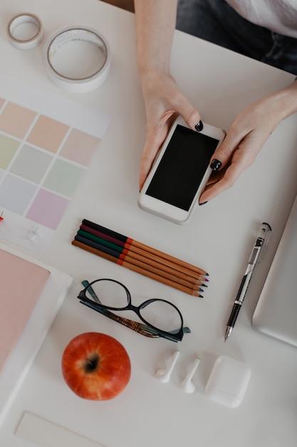 Portretfoto van kantoorbenodigdheden op wit en vrouwelijke handen met zwarte manicure, met smartphone. Gratis Foto