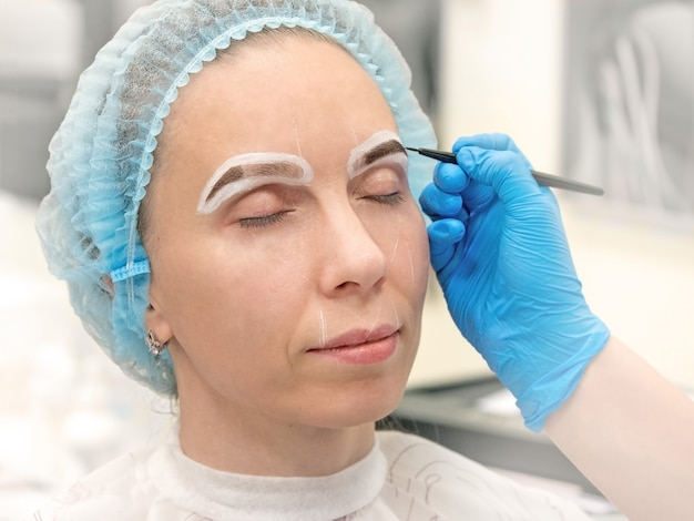 Portretfoto van vrouwen kleurende wenkbrauwen met henna in de schoonheidssalon. de architectuur van de wenkbrauw. Premium Foto