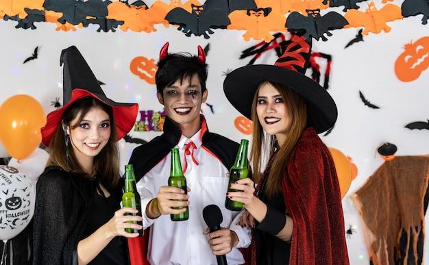 Portretgroep vrienden aziatische jonge volwassen mensen vieren halloween-feest. ze dragen halloween-kostuum, zingen een lied en juichen. halloween vieren en internationaal vakantieconcept Premium Foto