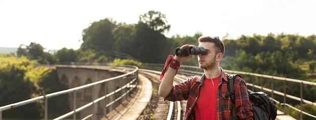 Portretmens die met rugzak met binoculair kijken Gratis Foto
